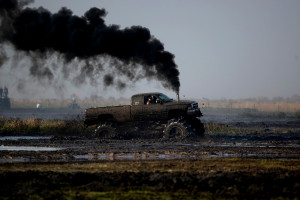 A diesel powered truck billows smoke as it rumbles through the mud bog.